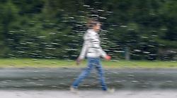THEMENBILD - ein Spaziergänger, durch eine mit Regentropfen benetzte Scheibe eines PKWs fotografiert, aufgenommen am 12.08.2014 in Kaprun, Österreich // a Women, photographed from behind a window, covered with rain drops during rainy weather in Kaprun, Austria on 2014/08/12. EXPA Pictures © 2014, PhotoCredit: EXPA/ JFK