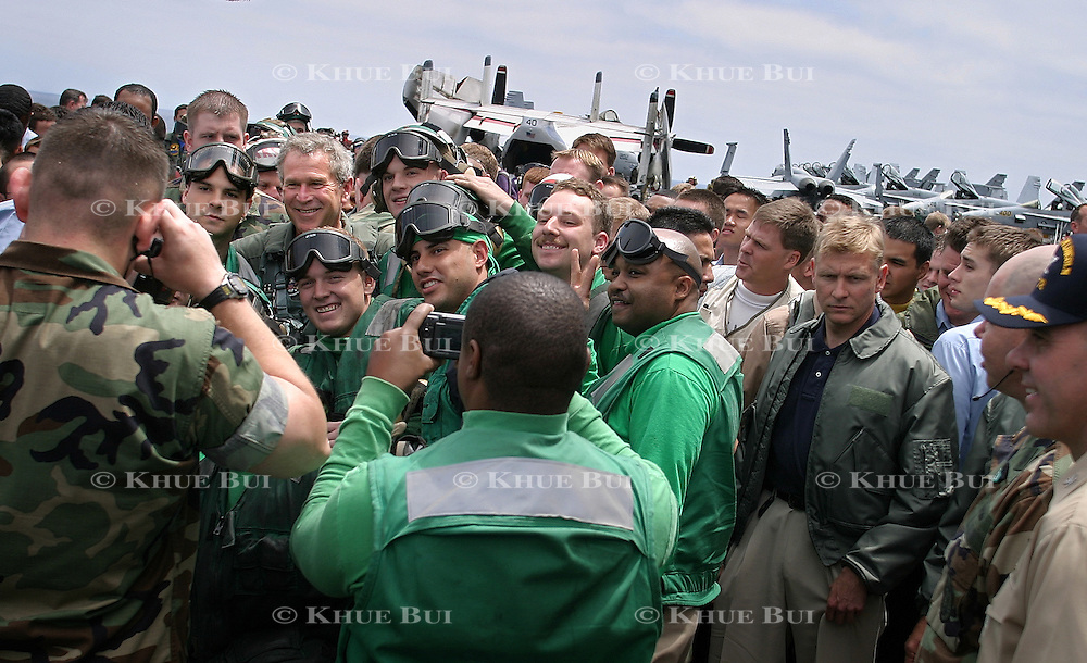 President Bush, wearing his flight suit, greets crew members on the flight deck of the aircraft carrier USS Abraham Lincoln after arriving via a US Navy S-3B Viking Thursday, May 1, 2003, in the Pacific Ocean.  Bush traveled to the aircraft carrier USS Abraham Lincoln to meet with returning sailors and to announce and end to 'major combat operations' in Iraq...Photo by Khue Bui