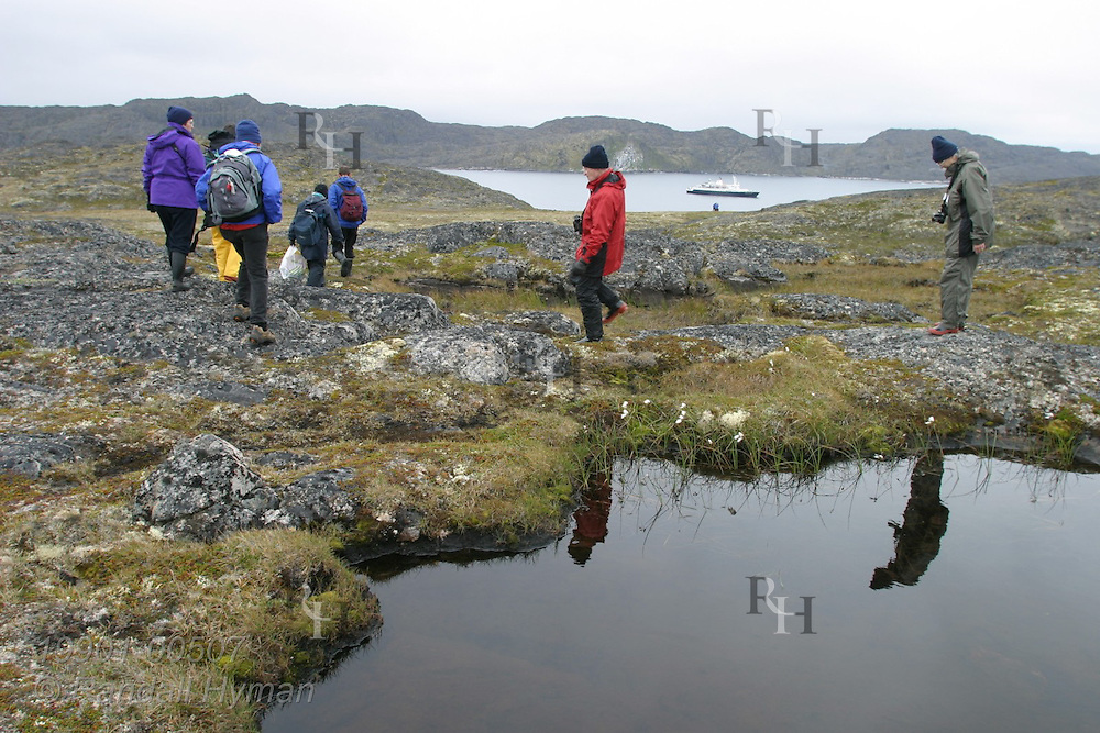 Rubber raft, or Zodiac, returns passengers to ship, Clipper Adventurer, after hike across rocky landscape of Eqalugssuit, Greenland