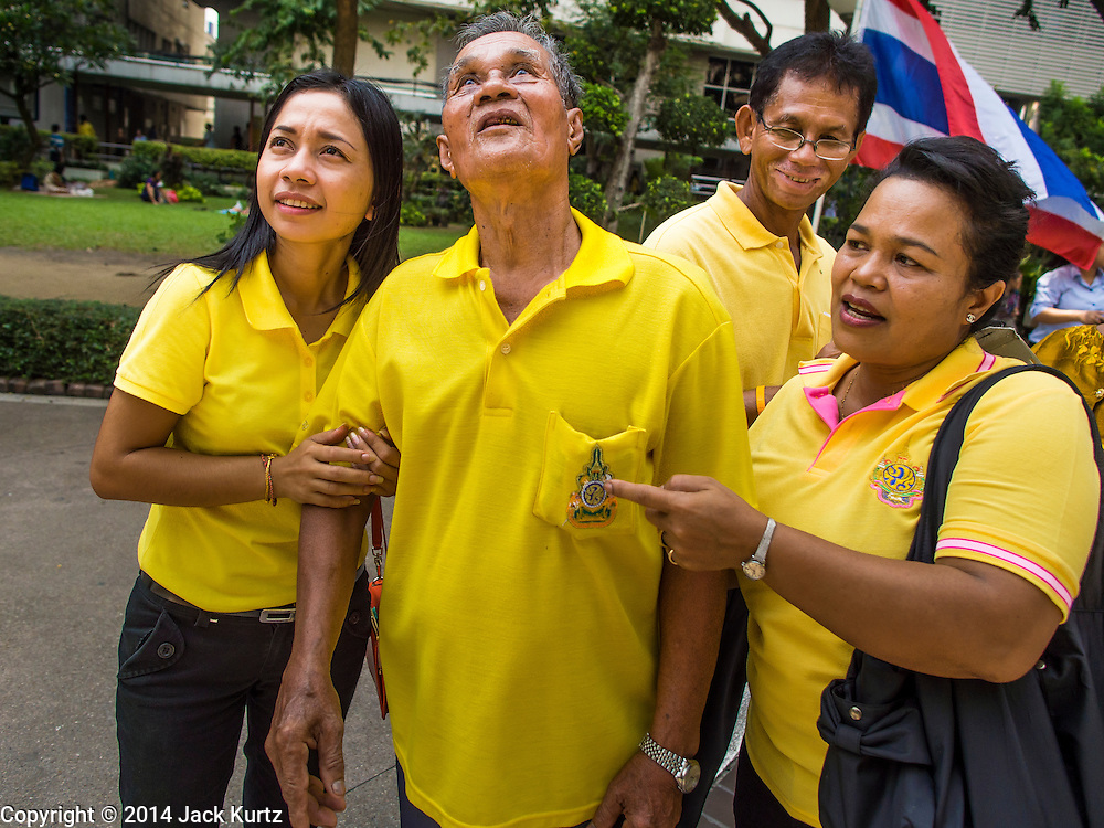 28 NOVEMBER 2014 - BANGKOK, THAILAND: A family at Siriraj Hospital looks up to the room Bhumibol Adulyadej, the King of Thailand, is staying in while they were at the hospital to offer prayers for the King. The King was born on December 5, 1927, in Cambridge, Massachusetts. The family was in the United States because his father, Prince Mahidol, was studying Public Health at Harvard University. He has reigned since 1946 and is the world's currently reigning longest serving monarch and the longest serving monarch in Thai history. Bhumibol, who is in poor health, is revered by the Thai people. His birthday is a national holiday and is also celebrated as Father's Day. He is currently hospitalized in Siriraj Hospital, recovering from a series of health setbacks. Thousands of people come to the hospital every day to sign get well cards for the King. People wear yellow at events associated with the King because he was born on a Monday, and yellow is Monday's color in Thai culture. It's also the color of the monarchy.       PHOTO BY JACK KURTZ