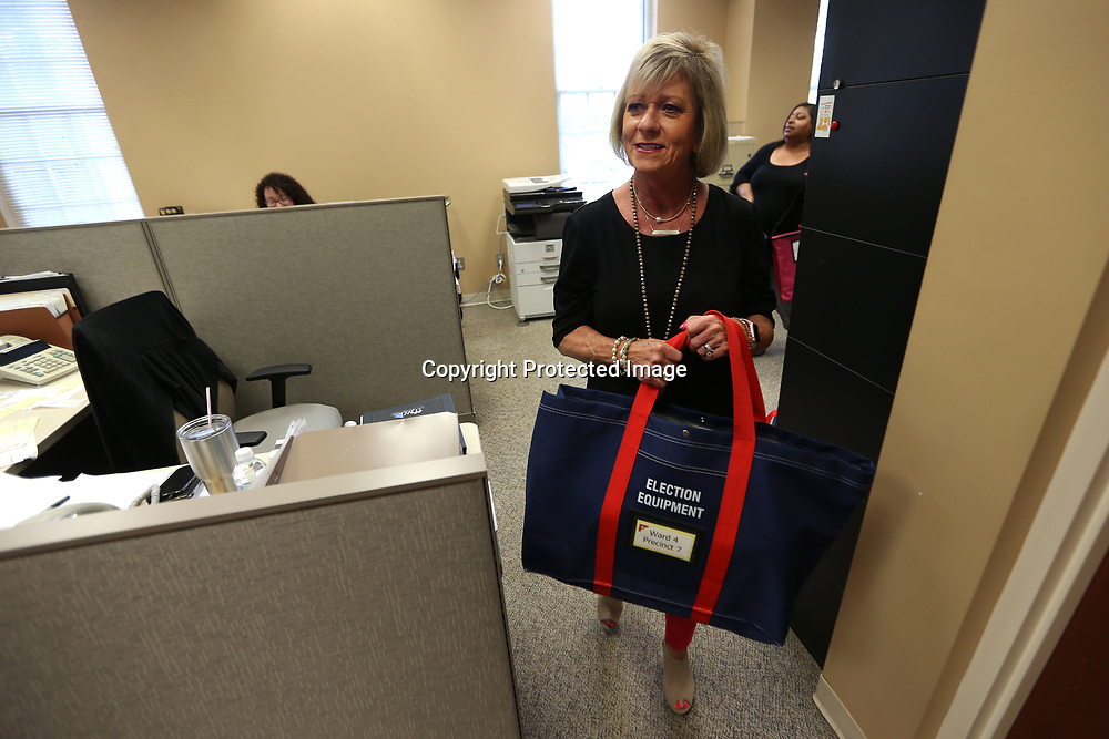 Beverly Dallas, a clerk for the city of Tupelo, carries a bag of election equipment to the from to be picked up by a returning and receiving manager for Tuesday's election in Tupelo.