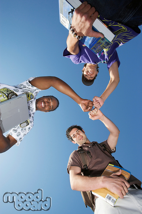 Three male college students with textbooks, view from below