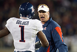 November 6, 2010; Stanford, CA, USA;  Arizona Wildcats head coach Mike Stoops talks with cornerback Robert Golden (1) on the sidelines during the second quarter against the Stanford Cardinal at Stanford Stadium.
