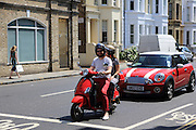 Man in red trousers on red moped in Chelsea, London