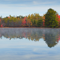 Early morning fog with reflection on lake in Acadia National Park, Maine.