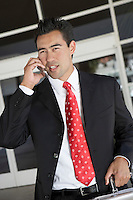 Businessman Using Cell Phone outside office half length