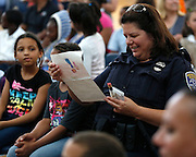 "Rochester Police officer Laurie Robinson reads a thank-you note that she received from Ciana Turner, 8, at left, at Enrico Fermi Elementary School No. 17 in Rochester on Monday, June 2, 2014. Officer Robinson helped tutor Turner, a second grader at School No. 17, in the ""Help Me Read"" program. The tutoring program helped 137 children improve their reading ability, with some students making jumps of several grade levels in one year."
