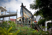 A fishing boat, which landed in a neighborhood from the 2004 tsunami, receives a make-over, and a platform for viewing, in Banda Aceh, Sunday, Nov. 8, 2009.