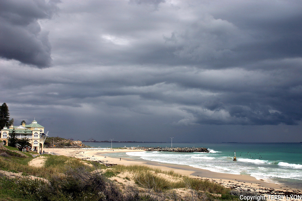 Thick almost black storm clouds cover the Indiana Restaurant and Cottesloe Beach.
