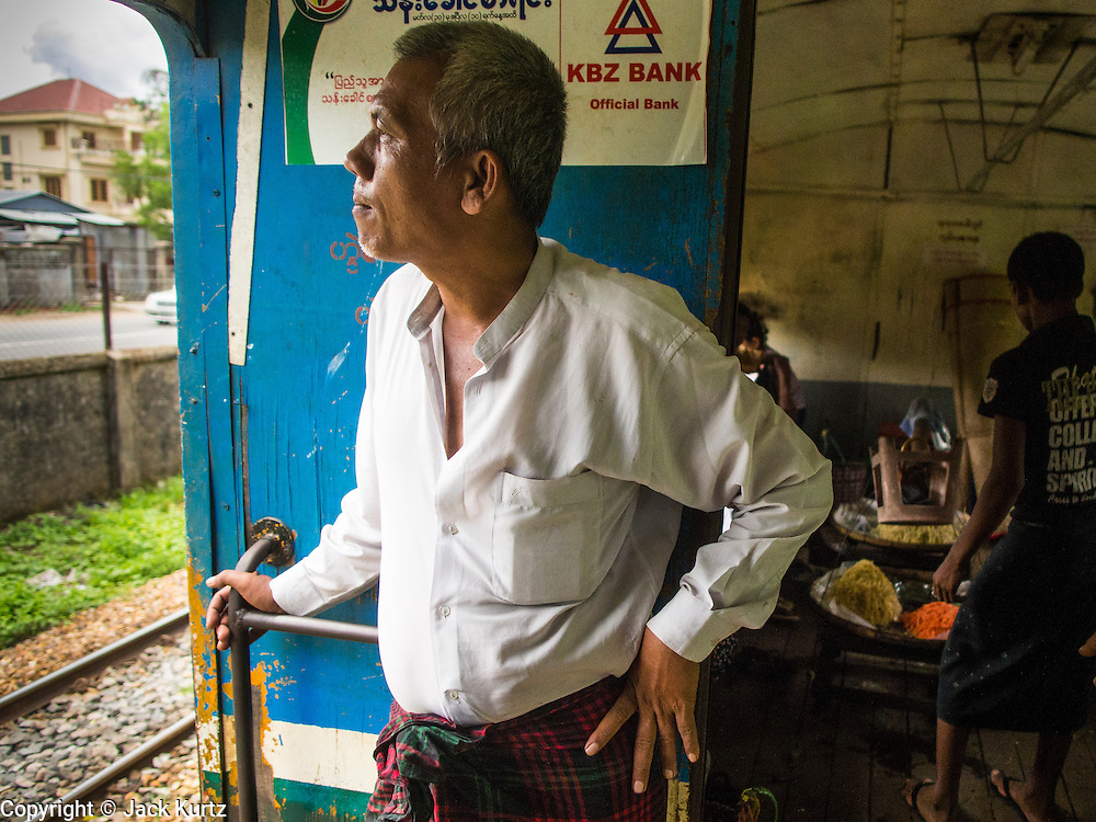 05 JUNE 2014 - YANGON, YANGON REGION, MYANMAR: A man looks out the door of the Yangon Circular Train as it rolls through the countryside. The Yangon Circular Train is a commuter train that circles Yangon, Myanmar (Rangoon, Burma). The train is 45 kilometers long, makes 38 stops and takes about three hours to make a loop of the city.     PHOTO BY JACK KURTZ