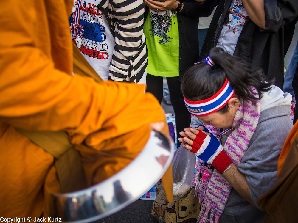 01 JANUARY 2014 - BANGKOK, THAILAND: An anti-government protestor prays after giving monks drinking water during a merit making ceremony. Thousands of anti-government protestors are camped out at Democracy Monument in central Bangkok protesting against the government of Yingluck Shinawatra. The protest leader, Suthep Thaugsuban, has called for residents of the Thai capital to rise up against Yingluck. He has promised to shut the city of 12 million down in his final push to overthrow the government. About 100 members of the Thailand's Buddhist clergy visited the protest site Wednesday morning for a special New Year's Day merit making ceremony for the protestors.     PHOTO BY JACK KURTZ