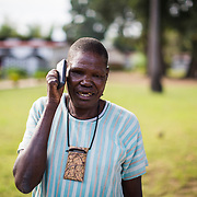 """The Bull"" can barely hold his mobile phone due to the damage done to his fingers by Leprosy. Ifakara, Tanzania"
