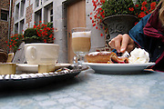 Belgium, An outdoor cafe close up of a woman eating apple cake with ice cream