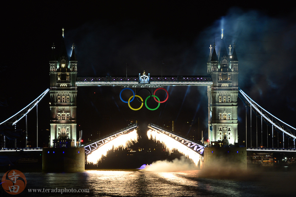 Jul 27, 2012; London, United Kingdom; The Olympic torch is transported on a boat on River Thames as fireworks light up the Tower Bridge during the opening ceremony.