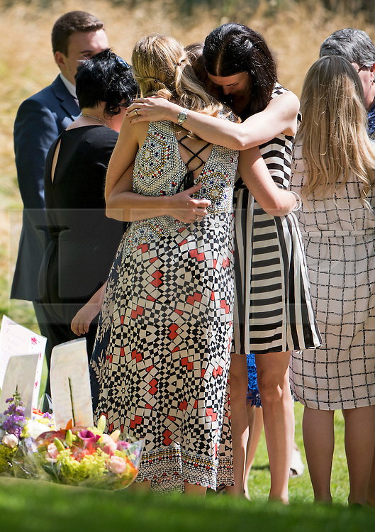 © Licensed to London News Pictures. 07/07/2015. London, UK. Family of those who lost their lives and survivors of the attack embrace after laying flower at the memorial during the service. A memorial service in Hyde Park London on the 10th anniversary of the 7/7 bombings in London. The event is attended by Prince William, survivors of the attack and family of those who lost their lives. Photo credit: Ben Cawthra/LNP