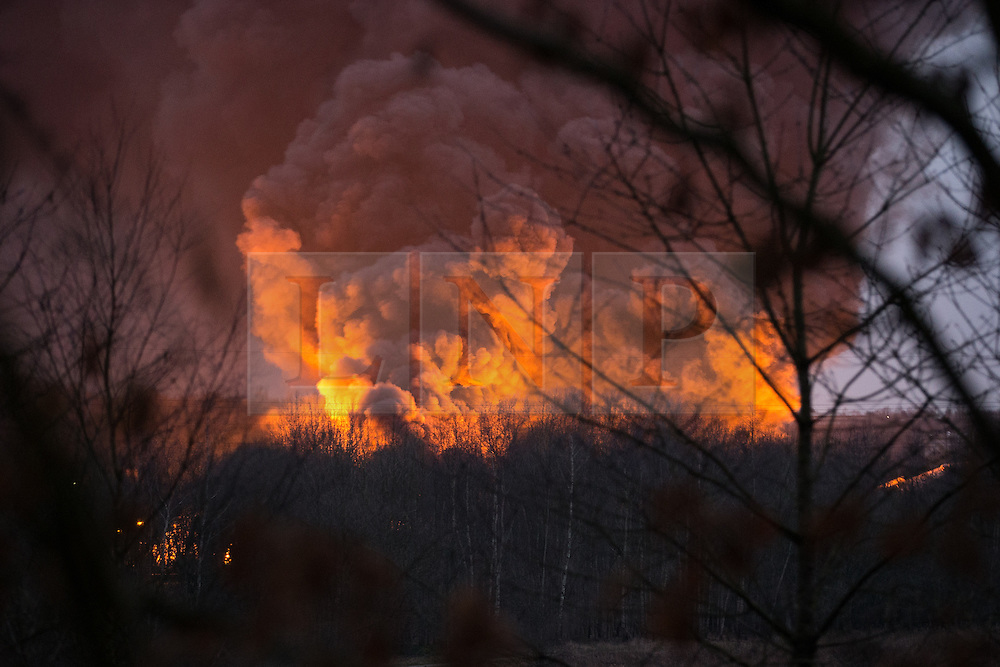 """© Licensed to London News Pictures . 15/03/2015 . Salford , UK . Roads are closed and people have been evacuated as a large fire burns at a unit within """" Junction Eco-Park """" in Clifton , Greater Manchester , this evening (Sunday 15th March 2015) . The smoke and flames can be seen for many miles . Forty fire fighters are at the scene working to control the blaze . Photo credit : Joel Goodman/LNP"""