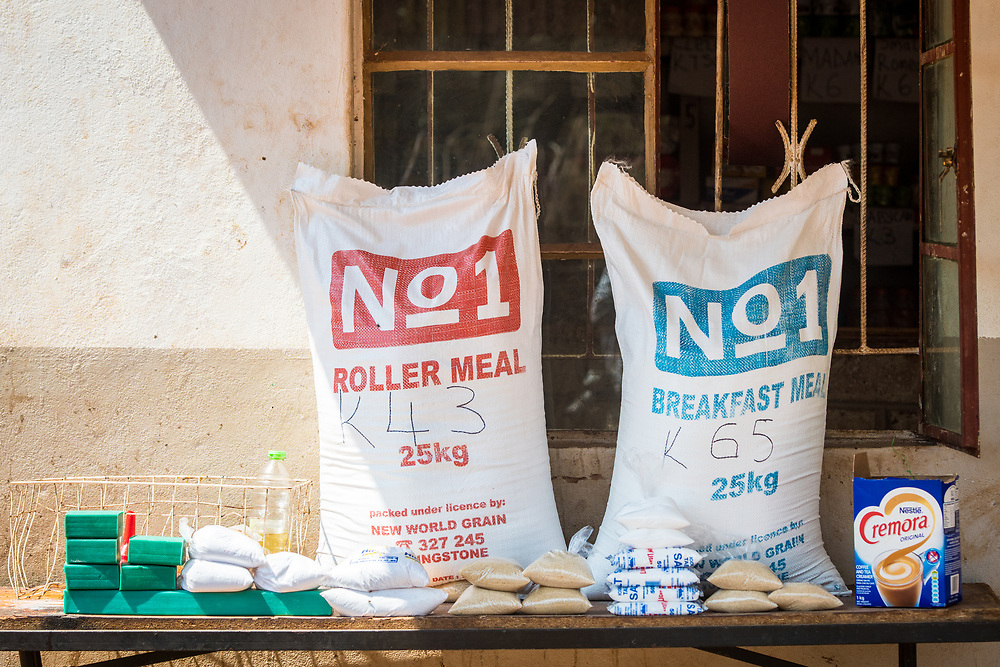Two large bags containing nonperishable food sit on top of table with other packaged foods, Mukuni Village, Zambia