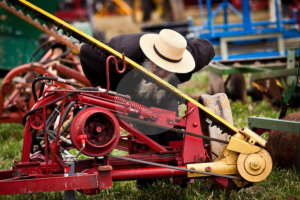 Elderly Amish man inspects farm equipment during the Annual Mud Sale to support the Fire Department  in Gordonville, PA.