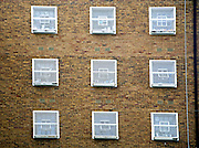 Cell windows of C wing. HMP Coldingley, Surrey was built in 1969 and is a Category C training prison. Coldingley is focused on the resettlement of prisoners and all prisoners must work a full working week within the prison. Its capacity is 390 prisoners.