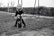 little girl posing with dog in the backyard Holland late 1960s
