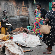 A Forestry Commission inspector chatting with market women while surrounded by illegal deliveries of bushbuck, duiker and wild pig at Atwemonom, the main bushmeat market in Kumasi, Ghana on 7 September 2016. A hunting ban was in effect, with grasscutters (greater cane rats) being the only legal quarry, but no action was taken and these deliveries were not recorded in his official logbook. One was noted on a separate scrap of paper together with an estimated value; for the others, false entries of grasscutters were logged.<br /> <br /> Ghana&rsquo;s bushmeat trade is estimated to be worth &pound;105 million a year.  Given a lack of current empirical data, it is hard to know how many wild animals are being killed to satisfy this demand, but between hunting and habitat loss it is clear that wildlife populations are declining precipitously. One estimate, now dated, posits that Ghana&rsquo;s wildlife biomass has declined by three-quarters since the 1970s.