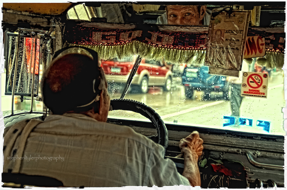 Reflection of a jeepney driver's wrinkled face in his rear view mirror. When American troops began to leave the Philippines at the end of WWII, hundreds of surplus jeeps were sold or given to local Filipinos, who stripped down and altered the jeeps to accommodate more passengers, added metal roofs for shade, and decorated the vehicles with vibrant colors and bright chrome hood ornaments. Most of these jeepneys have radically expanded passenger capacities, and are flamboyant and noisy. Many are notorious for belching smoke, and almost all are diesel, though efforts are underway to make these metal behemoths more efficient with alternative fuels.