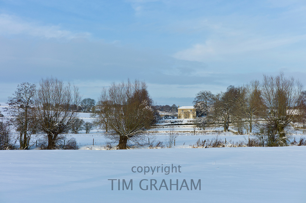 Georgian Manor House and snowy fields by the River Windrush in the village Swinbrook, The Cotswolds, UK