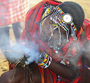Maasai Man lights a fire by rubbing two sticks and blowing on the tinder