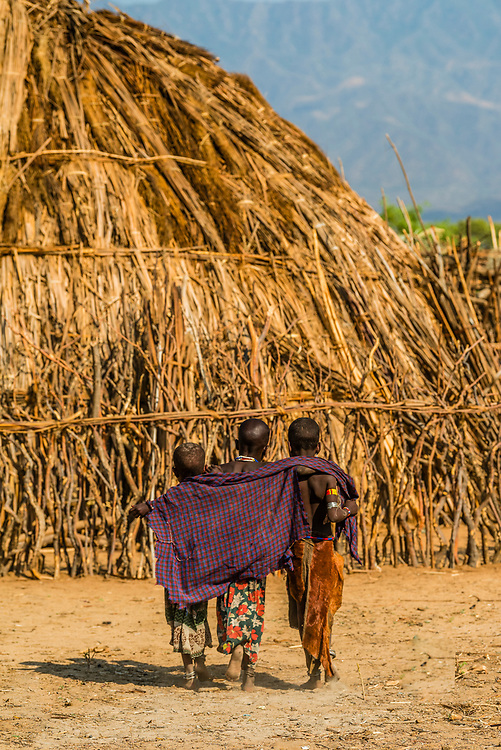 Arbore tribe girls walking arm in arm, Omo Valley, Ethiopia.