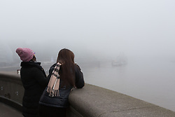 © Licensed to London News Pictures. 17/12/2016. LONDON, UK.  Two tourists try to look at HMS Belfast on the River Thames this morning. London and the River Thames was shrouded in thick fog this morning.  Photo credit: Vickie Flores/LNP