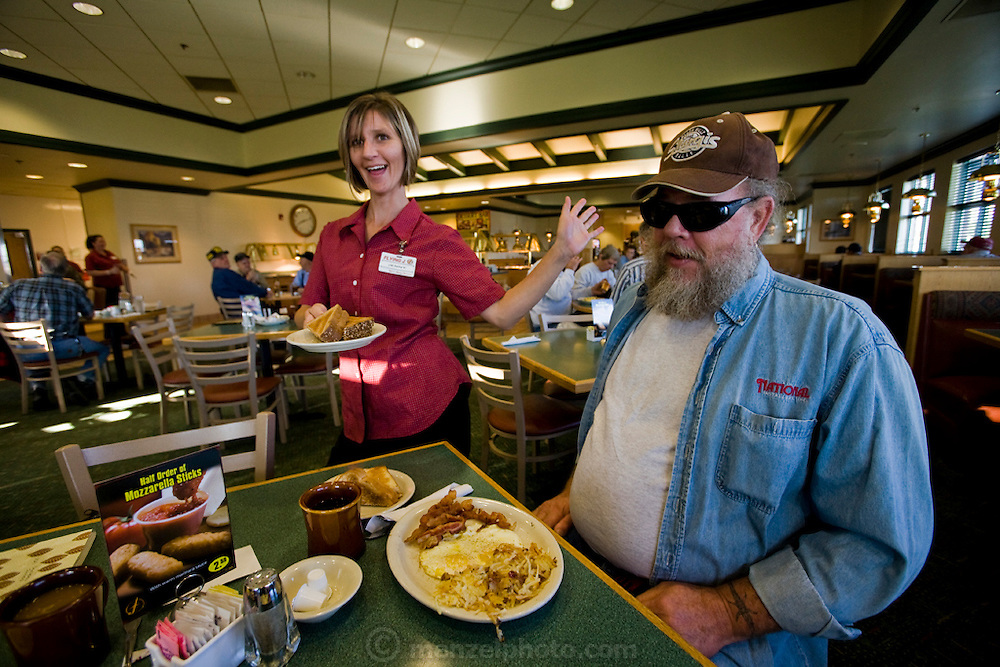 A waitress stands next to truck driver and former biker Conrad Tolby as he begins to eat his breakfast in a restaurant at a truck stop at the intersection of I-70 and I-57 in Effingham, Illinois. (Conrad Tolby is featured in the book What I Eat: Around the World in 80 Diets.) MODEL RELEASED.