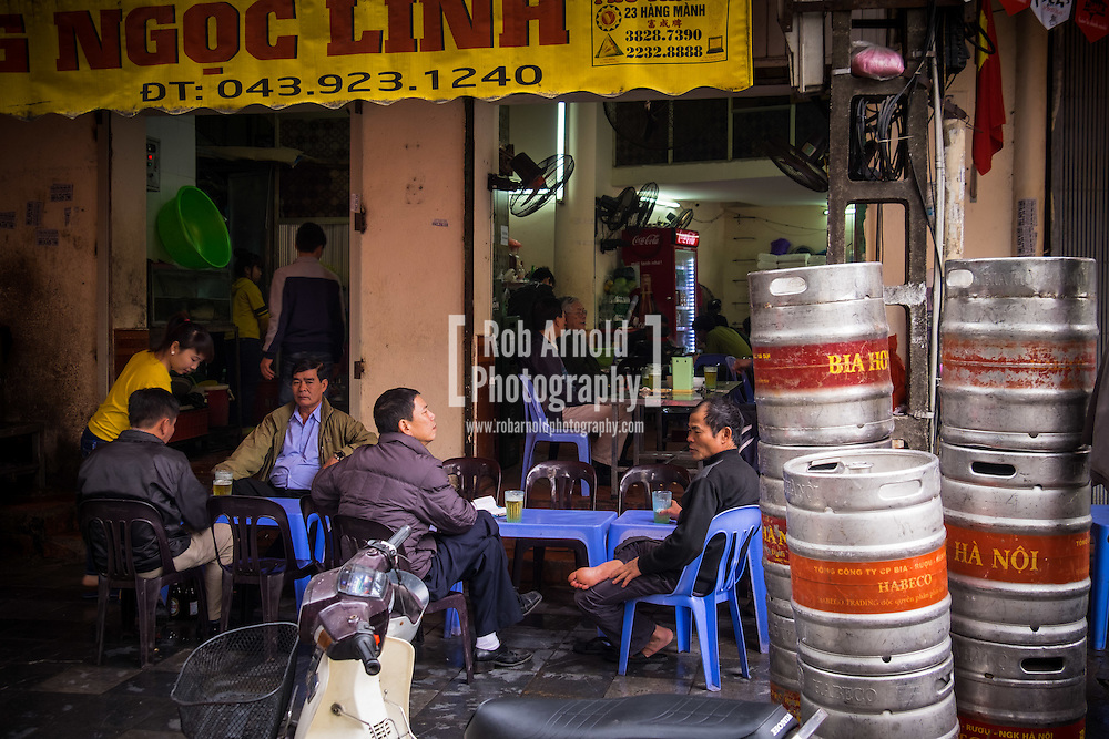 A group of men enjoying a Bia Hoi Hanoi (Hanoi Fresh Beer) in Hanoi's Old Quarter.