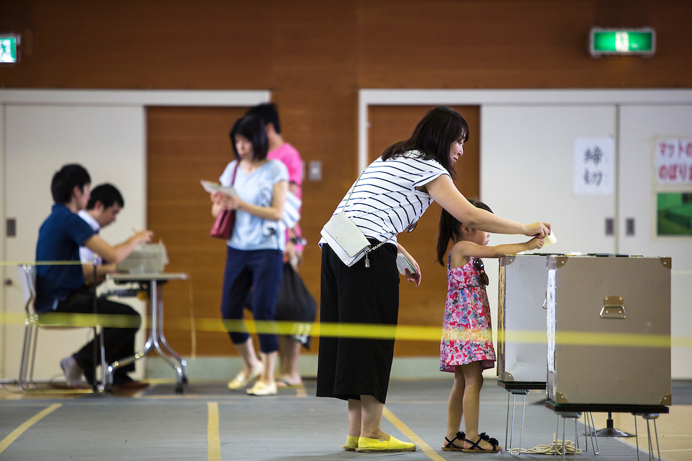 TOKYO, JAPAN - JULY 10 : A woman with her daughter cast her ballots to vote for parliament's upper house election at a polling station in Tokyo, Japan on Sunday, July 10, 2016. The revised law has expanded the electorate by 2.4 million people aged 18 and 19, and is designed to give more political say to younger generations. The first Upper house election nation-wide in Japan that 18 years old can vote after government law changes its voting age from 20 years old to 18 years old.  (Photo by Richard Atrero de Guzman/NUR Photo)