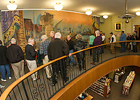 Guests gather around the Moulton Opera House curtain during the Opening Reception and unveiling at the Laconia Library on Wednesday evening.  (Karen Bobotas/for the Laconia Daily Sun)