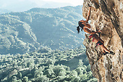 Marture strong woman climber climbing a overhanging limestone wall with tufas Mamut climbing athlete Bobbi Bensman enjoying a climbing trip at Roca Verde, Asturias, Spain