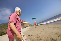 Two Men Throwing Frisbee on Beach
