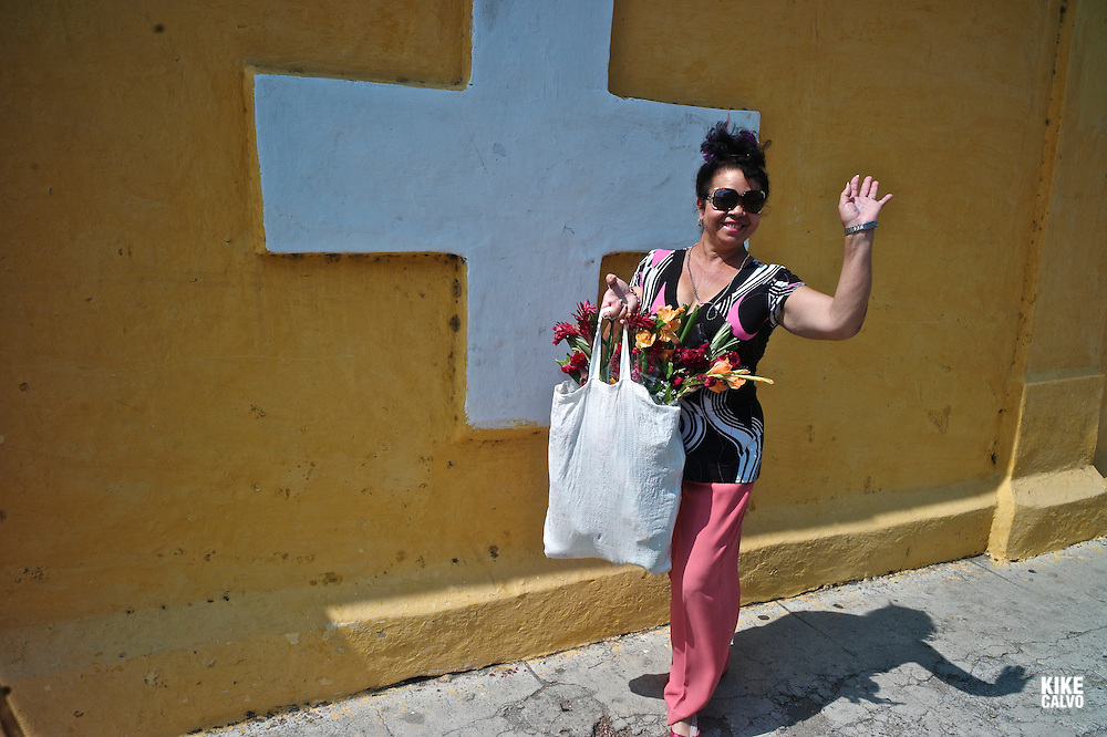 Happy Cuban woman bringing flowers for Mother Day to the cementery of Colon in Vedado