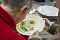 Visually impaired people with carers on outing to Denby Pottery. Inspecting glaze.