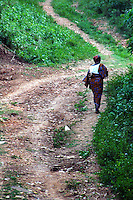 Ghana, Adaklu, Titikope, 2007. A mother takes the long road up away from the Volta River and back toward her family home.