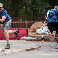 Chris Barber from the Dolores, Colorado Fire Protection District races to unfurl a hose during the annual Tristate Firefighters Association games at Red Rock Park in Gallup Friday.