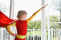 Portrait of young boy (7-9) wearing superhero costume arm raised indoors