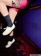 A girl dancing, wearing a bright colourful leotard and plimsoles, The Junk Club, Southend, UK 2006