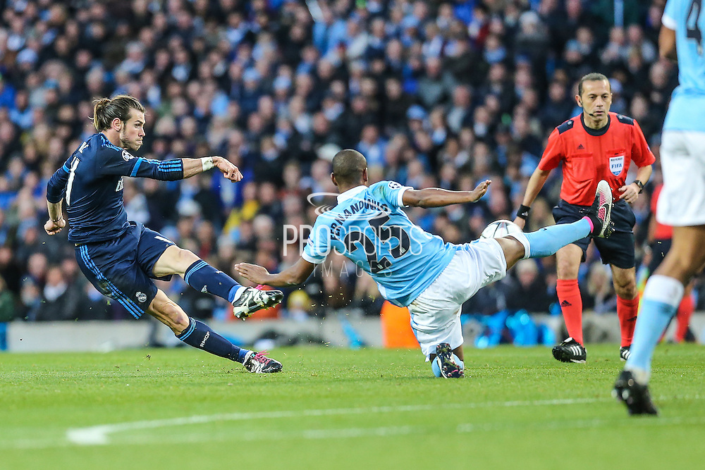 Real Madrid's Gareth Bale has a shot at goal blocked by Manchester City's Fernandinho during the Champions League match between Manchester City and Real Madrid at the Etihad Stadium, Manchester, England on 26 April 2016. Photo by Shane Healey.