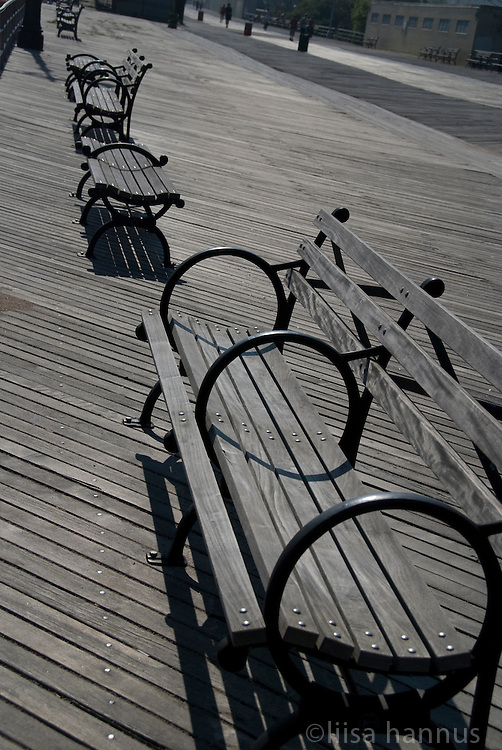 Empty wooden benches line the boardwalk at Coney Island, in Brooklyn, New York.