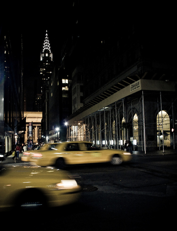 Yellow taxicabs stream by on a midtown Manhattan street near the Chrysler Building, New York, USA.