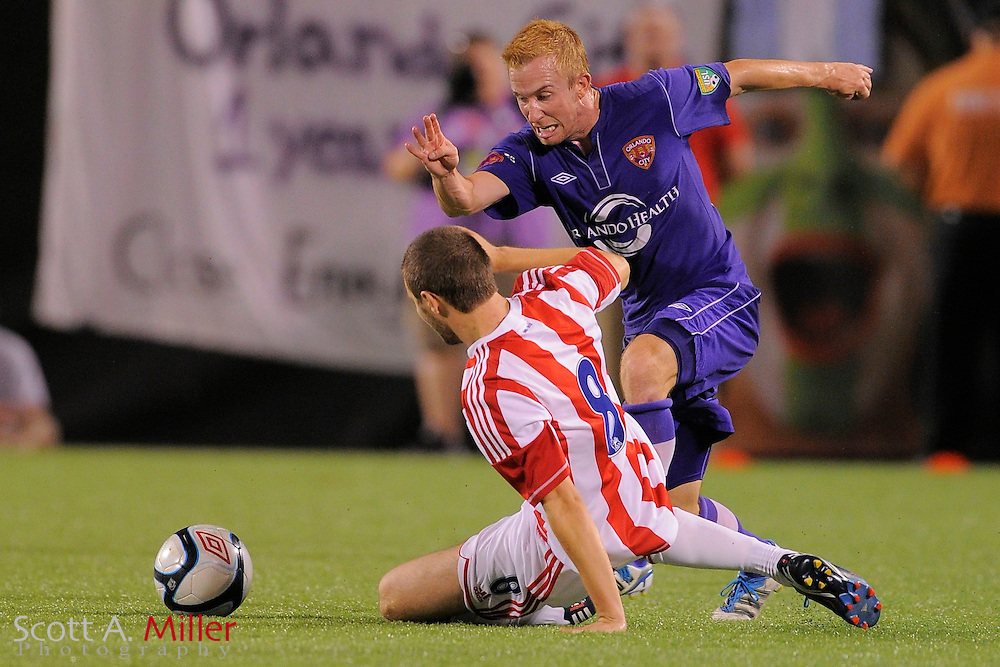 Orlando City Lions midfielder James O'Connor (17) and Stoke City Potters midfielder Jamie Ness (8) go for a ball at the Florida Citrus Bowl on July 28, 2012 in Orlando, Florida. Stoke won 1-0...© 2012 Scott A. Miller.