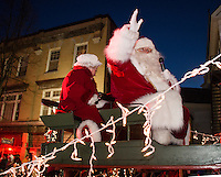 Santa and Mrs. Claus wave to the crowd as their float makes its way down Main Street during the annual holiday parade and tree lighting on Sunday evening.  (Karen Bobotas/for the Laconia Daily Sun)