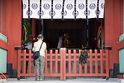 A man prays in front of the inner sanctuary -- in front of which seaweed has been draped -- during the annual Reitaisai Grand Festival at Tsurugaoka Hachimangu Shrine in Kamakura, Japan on  14 Sept. 2012.  Sept 14 marks the first day of the 3-day Reitaisai festival, which starts early in the morning when shrine priests and officials perform a purification ritual in the ocean during a rite known as hamaorisai and limaxes with a display of yabusame horseback archery. Photographer: Robert Gilhooly