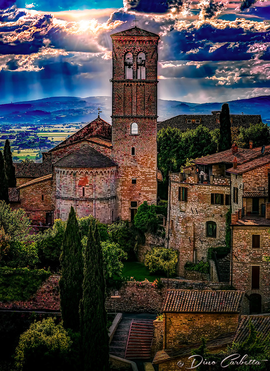"""""""The light of God falls on the bell tower of Santa Maria Maggiore – Assisi""""…<br /> <br /> After a progressive but slow ascent up to the mountaintop of Assisi, I took time to pause, look over my shoulder, and truly appreciate all I had seen. God always seemed to illuminate my forward path; however, He also left a glow of remembrance from where the journey began. This evening view is from the Basilica di Santa Chiara (Basilica of St. Clare), a 13th-century church that houses the relics of St. Clare, friend and protégé of St. Francis of Assisi, and the 12th-century crucifix that spoke to St. Francis at San Damiano. The view is a rear view of the church and campanile of Santa Maria Maggiore, the first cathedral of Assisi which was built near the Roman city walls of the 4th century. The crypt under the apse of the present church is the oldest surviving part of the structure and dates to the 9th or 10th century. Santa Maria Maggiore remained the cathedral of Assisi until 1035 when San Rufino assumed this function."""