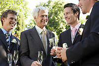 Four men holding empty wineglasses smiling
